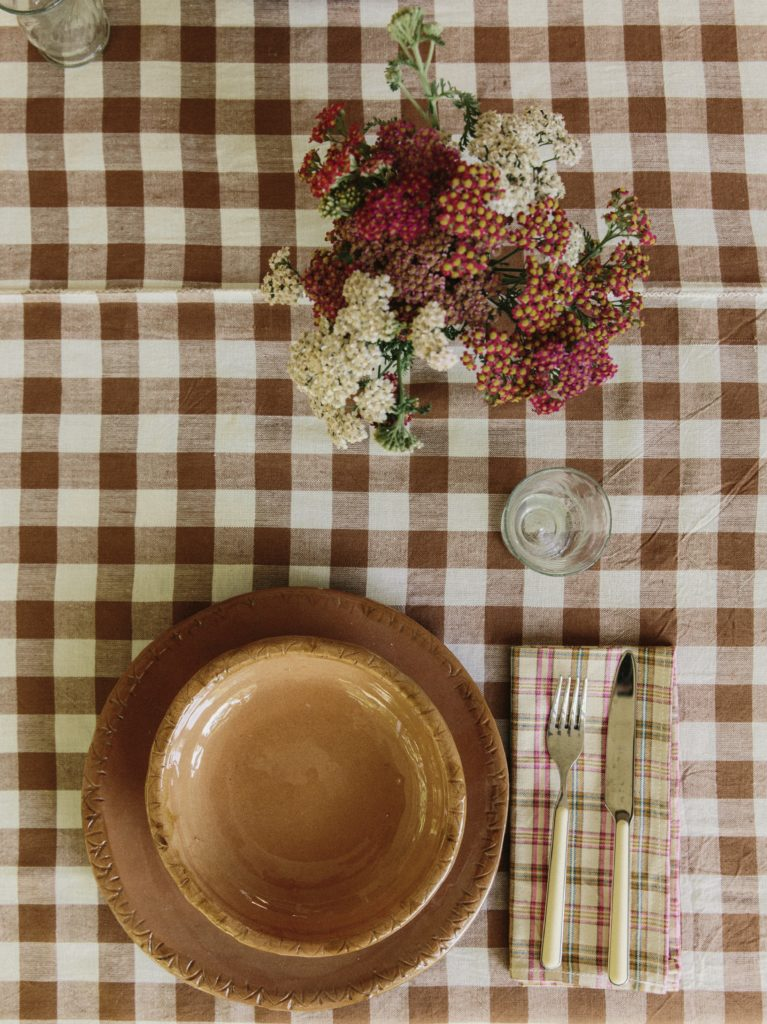 brown checkered tablecloth with a tan ceramic plate, pink and brown plaid napkin next to it and wildflowers
