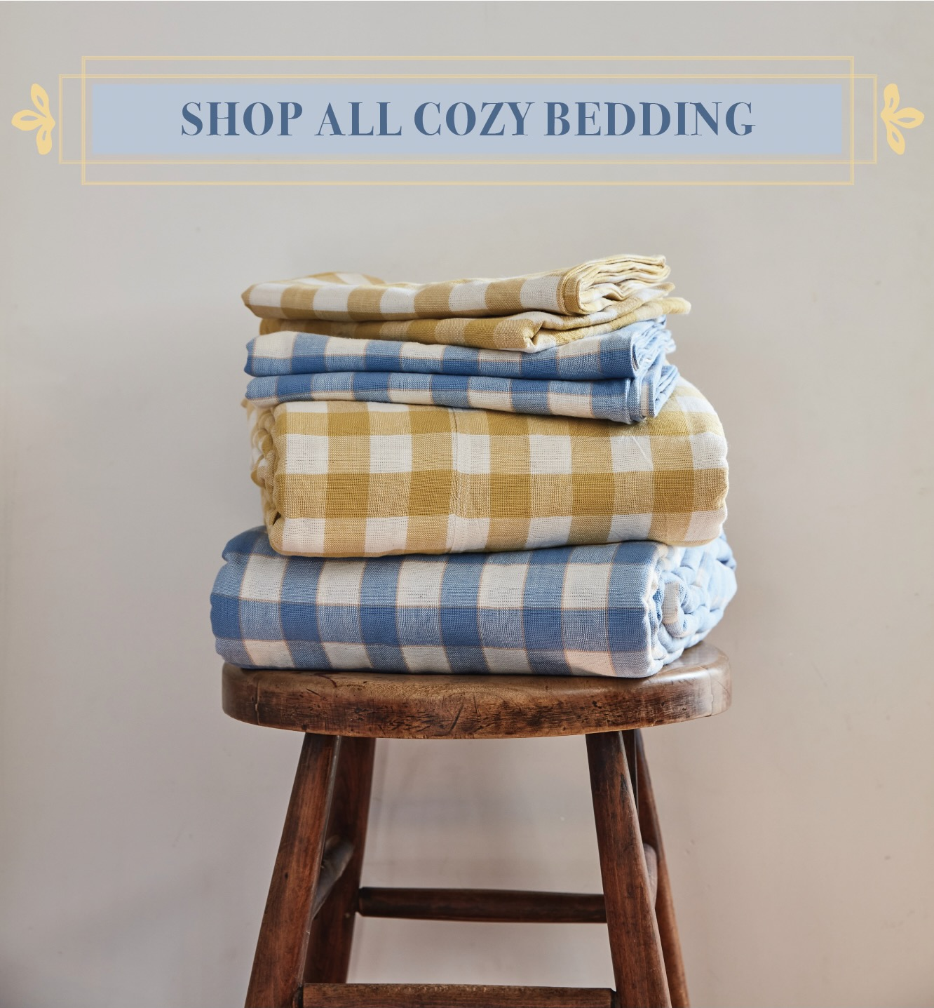 """Blue text with a yellow outline that reads: """"Shop all cozy bedding!"""" The text is overlaid on an image of bedding linens stacked on top of a wooden stool. The linens are sunflower yellow and white gingham duvet cover and pillowcases stacked together with matching blue and white gingham duvet cover and pillowcases."""